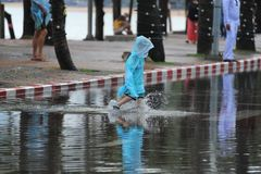 Niño que lleva el impermeable azul que camina en la inundación fotografía de archivo