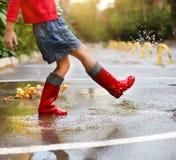 Niño que lleva las botas de lluvia rojas que saltan en un charco Foto de archivo