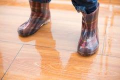 Niño que lleva los gumboots impermeables que se colocan en piso mojado Fotos de archivo libres de regalías