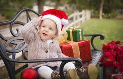 Niño que lleva a Santa Hat Sitting con los regalos de la Navidad afuera Imagenes de archivo