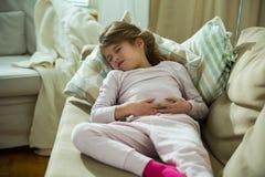 Niño que miente en el sofá en la sala de estar con dolor de estómago imagen de archivo