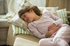Niño que miente en el sofá en la sala de estar con dolor de estómago foto de archivo