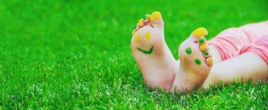 Niño que miente en hierba verde Niño que se divierte al aire libre en parque de la primavera Imagen de archivo