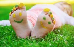 Niño que miente en hierba verde Niño que se divierte al aire libre en parque de la primavera Fotografía de archivo libre de regalías