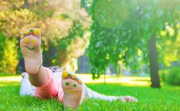 Niño que miente en hierba verde Niño que se divierte al aire libre en parque de la primavera Imágenes de archivo libres de regalías