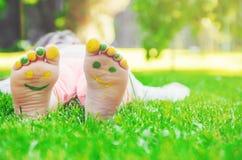 Niño que miente en hierba verde Niño que se divierte al aire libre en parque de la primavera Fotografía de archivo