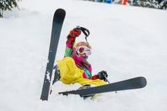 Niño que miente en nieve con los esquís Fotos de archivo