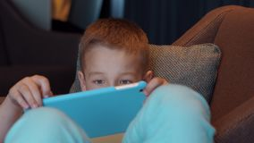 Niño que miente en silla del brazo e historietas de observación en el cojín almacen de metraje de vídeo