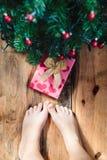 Niño que mira abajo actualmente debajo del árbol de navidad Fotografía de archivo