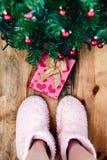 Niño que mira abajo actualmente debajo del árbol de navidad Foto de archivo libre de regalías