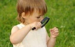 Niño que mira el caracol a través de la lupa Fotografía de archivo libre de regalías