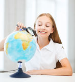 Niño que mira el globo con la lupa Fotos de archivo
