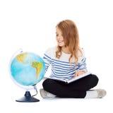 Niño que mira el globo y que sostiene el libro Foto de archivo libre de regalías