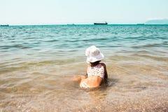 Niño que mira el mar y las naves foto de archivo