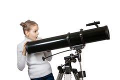 Niño que mira en la estrella del telescopio que mira a la niña Fotos de archivo