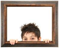 Niño que mira a escondidas de marco de madera adornado imagen de archivo libre de regalías