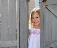 Niño que mira a escondidas hacia fuera de detrás una puerta Imágenes de archivo libres de regalías