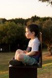 Niño que mira fijamente la puesta del sol Imagenes de archivo