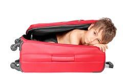 Niño que mira hacia fuera la maleta roja Imagenes de archivo