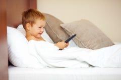 Niño que mira historietas de la TV en cama foto de archivo
