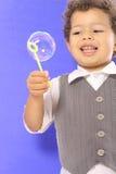 Niño que mira la cara de la burbuja Imagen de archivo