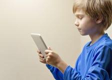 Niño que mira la tableta digital y que juega los juegos onlines, el aprendizaje o la lectura Cierre para arriba Imagen de archivo