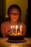 Niño que mira las velas en el cumpleaños Imagen de archivo
