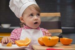 Niño que mira para arriba en sorpresa pequeña muchacha linda del retrato en traje del cocinero con la naranja De 2 años Fotografía de archivo