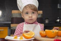 Niño que mira para arriba en sorpresa pequeña muchacha linda del retrato en traje del cocinero con la naranja De 2 años Foto de archivo