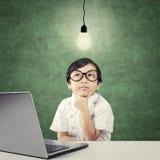 Niño que mira para arriba la lámpara con el ordenador portátil en la tabla Fotos de archivo libres de regalías