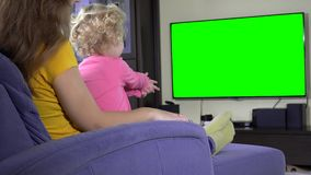 Niño que mira programa de la TV con la mamá Pantalla verde de la llave de la croma metrajes
