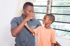 Niño que mira a su padre beber el agua Imagenes de archivo