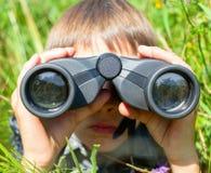 Niño que mira a través de los prismáticos Imagenes de archivo