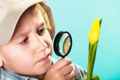 Niño que mira a través de una lupa Fotografía de archivo libre de regalías