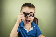 Niño que mira a través de una lupa fotos de archivo