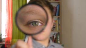 Niño que mira a través de una lupa almacen de video