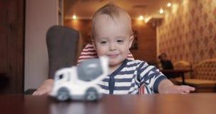 Niño que mira un coche del juguete el sentarse en una silla del bebé metrajes