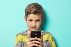 Niño que mira un teléfono celular con una mirada sorprendida en su cara Imagen de archivo