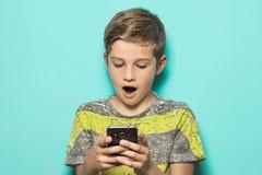 Niño que mira un teléfono celular con una mirada sorprendida en su cara Fotos de archivo