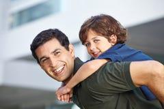 Niño que monta a cuestas en su padre Imágenes de archivo libres de regalías
