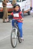 Niño que monta la bicicleta con entusiasmo en el paseo del día de la república Imágenes de archivo libres de regalías