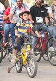 Niño que monta la bicicleta con entusiasmo en el paseo del día de la república Fotos de archivo
