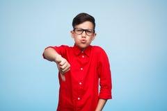 Niño que muestra el pulgar abajo Fotografía de archivo libre de regalías