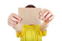 Niño que muestra la cartulina en blanco Fotos de archivo
