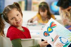 Niño que muestra la pintura en clase de arte Imagen de archivo libre de regalías