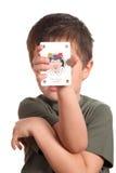 Niño que muestra la tarjeta que juega del bromista Imagen de archivo