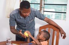Niño que muestra una manzana a su padre Imagen de archivo libre de regalías