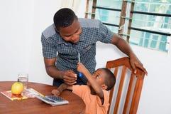 Niño que muestra una pluma a su profesor casero Fotos de archivo libres de regalías