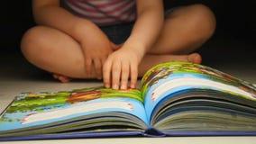 Niño que mueve de un tirón el libro El libro de niños con las imágenes coloridas almacen de video