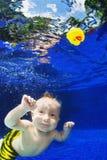 Niño que nada bajo el agua en la piscina azul para el juguete amarillo fotos de archivo